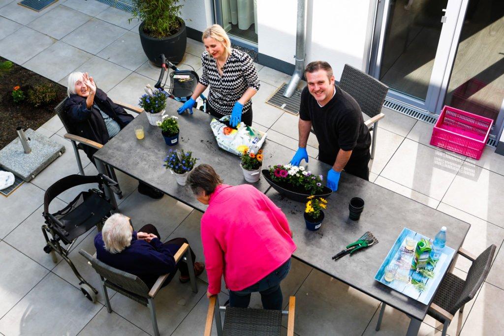 Blumen für den Innenhof setzen Betreuer und Mieter der Senioren-WG am Südertor gemeinsam in die Erde.